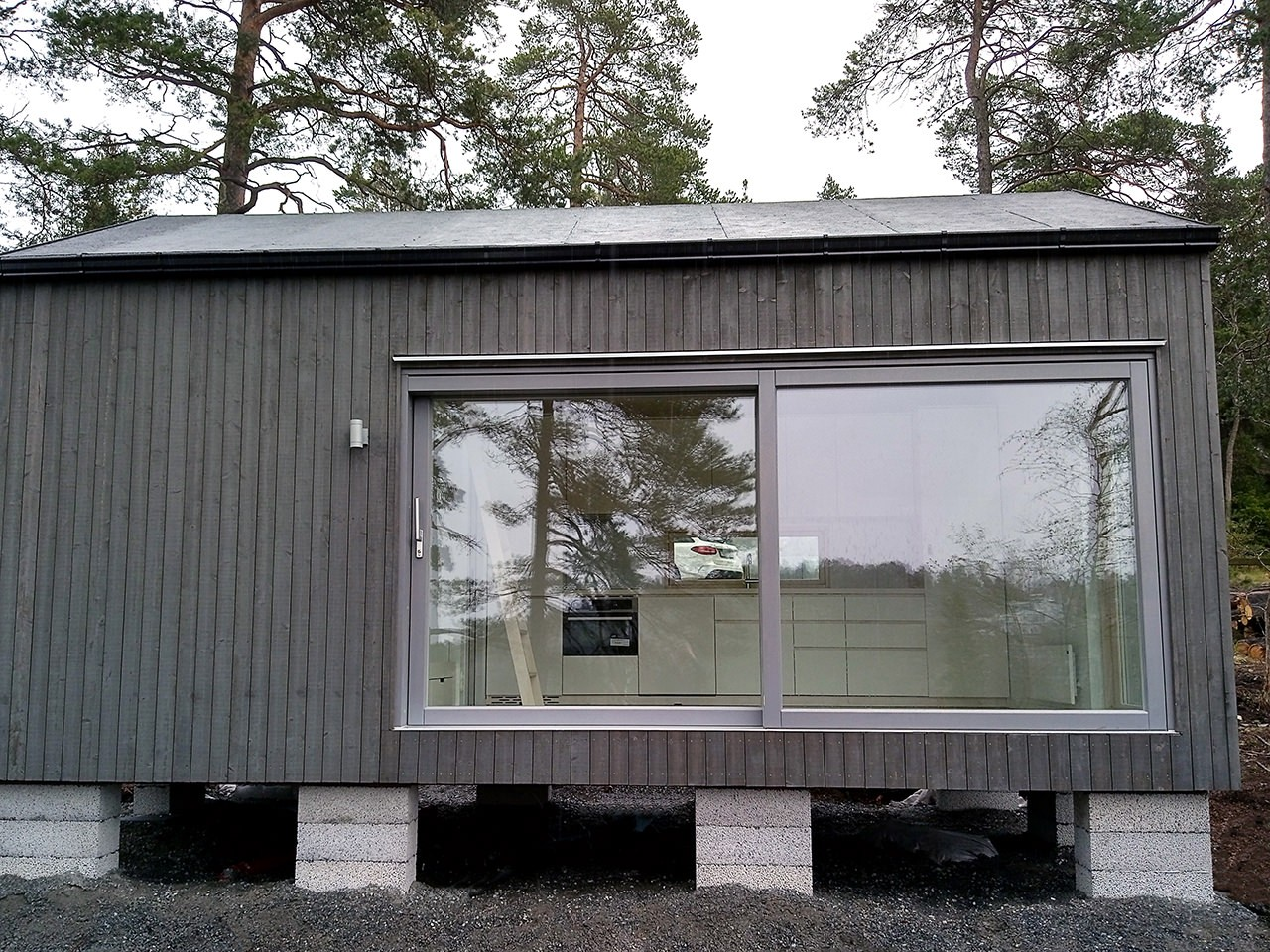 fritidshus bred skjutdörr tjärvitriol fasad